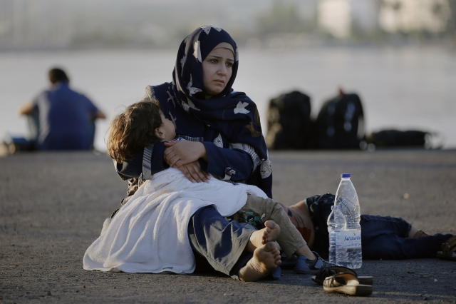 "A Syrian refugee holds her child in her arms as she sits in the port of the Greek island of Kos waiting to be registered and move with her family to the ""Eleftherios Venizelos"" vessel August 15, 2015. United Nations refugee agency (UNHCR) called on Greece to take control of the ""total chaos"" on Mediterranean islands, where thousands of migrants have landed. About 124,000 have arrived this year by sea, many via Turkey, according to Vincent Cochetel, UNHCR director for Europe. REUTERS/Yannis Behrakis - RTX1OCU3"