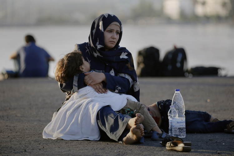 """A Syrian refugee holds her child in her arms as she sits in the port of the Greek island of Kos waiting to be registered and move with her family to the """"Eleftherios Venizelos"""" vessel August 15, 2015. United Nations refugee agency (UNHCR) called on Greece to take control of the """"total chaos"""" on Mediterranean islands, where thousands of migrants have landed. About 124,000 have arrived this year by sea, many via Turkey, according to Vincent Cochetel, UNHCR director for Europe. REUTERS/Yannis Behrakis - RTX1OCU3"""