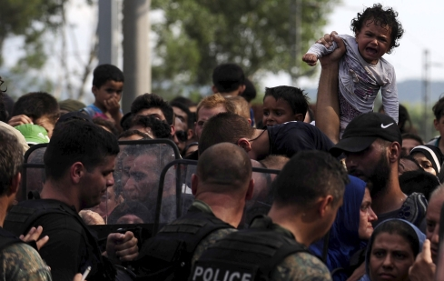 A baby cries at the border line dividing Macedonia and Greece August 21, 2015. At least 1,000 migrants and refugees pressed against Macedonian police lines on the Greek-Macedonian border on Friday and at least 10 people appeared to faint in the crush. People could be heard screaming and medical workers raced to treat those who passed out or were hurt. The crush ensued after police let several hundred through into Macedonia, having kept them out since Thursday under an emergency decree. REUTERS/Ognen Teofilovski - RTX1P3HW