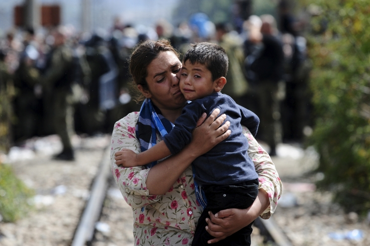 A woman carries a boy after crossing Greece's border into Macedonia near Gevgelija, Macedonia, August 22, 2015. Thousands of migrants stormed across Macedonia's border on Saturday, overwhelming security forces who threw stun grenades and lashed out with batons in an increasingly futile bid to stem their flow through the Balkans to western Europe. Some had spent days in the open with little or no access to food or water after Macedonia on Thursday declared a state of emergency and sealed its borders to migrants, many of them refugees from war in Syria and other conflicts in the Middle East. REUTERS/Ognen Teofilovski  - RTX1P7YZ